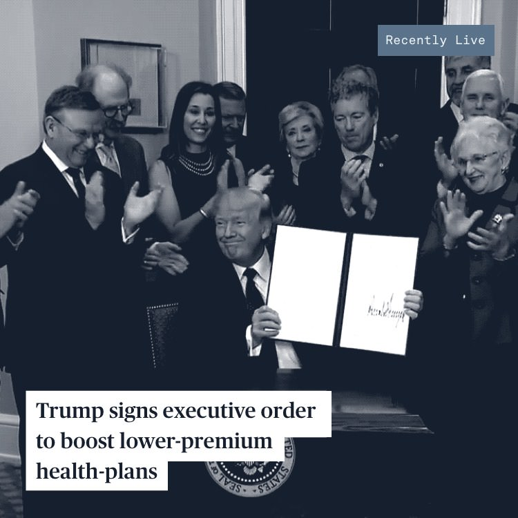 President Trump shows his signature on an executive order while a group of politicians clap behind him.